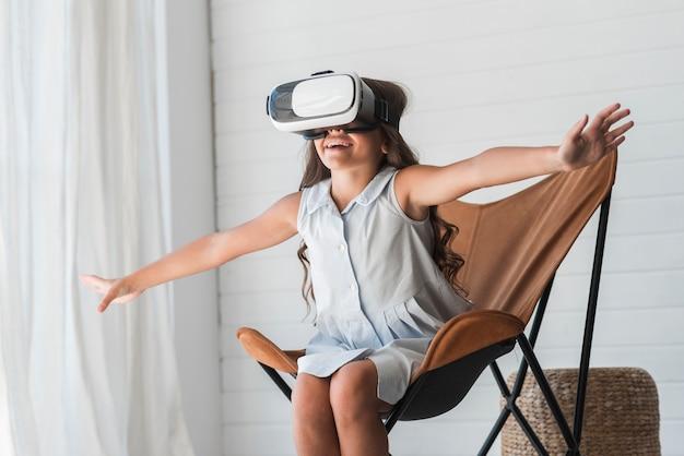 Ragazza stupita che si siede sulla sedia che indossa i vetri di realtà virtuale a casa