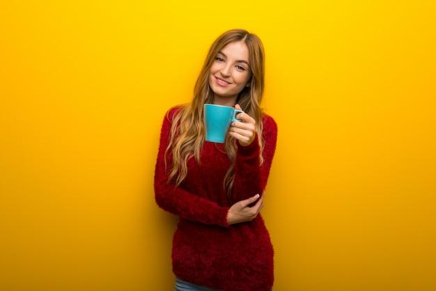 Ragazza su giallo vibrante che tiene una tazza di caffè calda