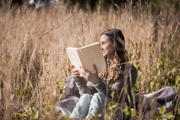 Ragazza su un campo che legge un libro