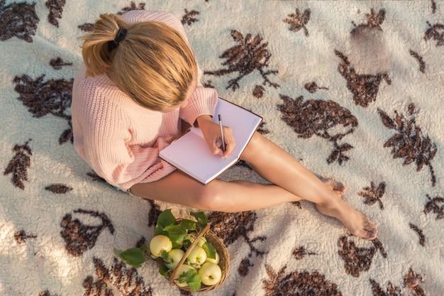 Ragazza su un picnic sulla natura riposa su una coperta di coperte