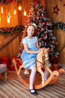 Ragazza sul cavallo di legno del giocattolo vicino all'albero di natale