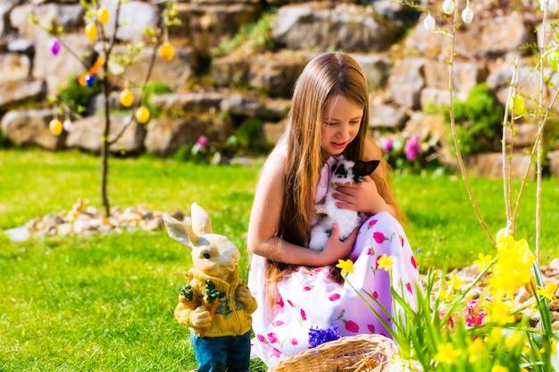 Ragazza sulla caccia alle uova di pasqua con coniglietto di pasqua vivente