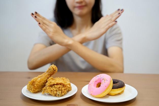 Ragazza sulla dieta che rifiuta cibo spazzatura incrociando le sue mani su di loro.