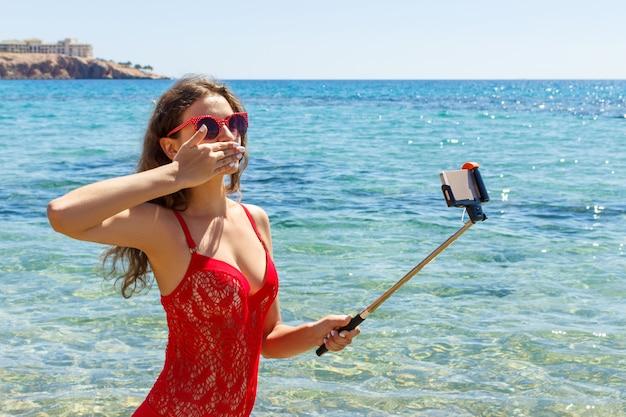 Ragazza sulla spiaggia con un telefono cellulare che fa selfie il giorno soleggiato