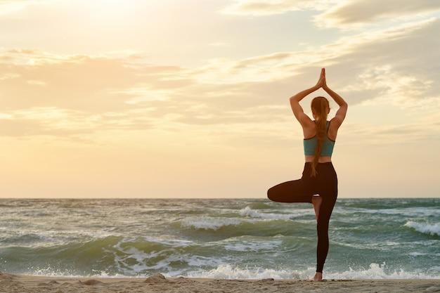 Ragazza sulla spiaggia del mare praticare lo yoga. vista posteriore. bella luce del sole