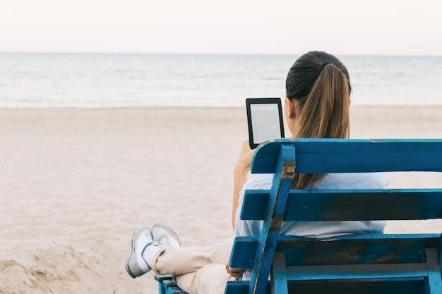 Ragazza sulla spiaggia leggendo un libro seduto sulla panchina