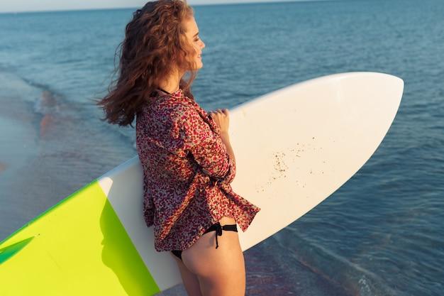 Ragazza surfista sulla spiaggia