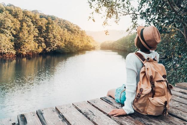 Ragazza sveglia che backpacking e che si siede sulla plancia di legno che riposa e che osserva sul fiume.