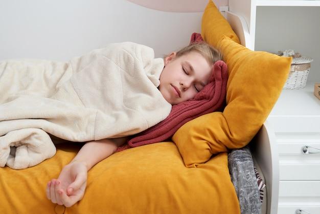 Ragazza sveglia che dorme nel letto avvolto in coperta molle, concetto di sogni d'oro