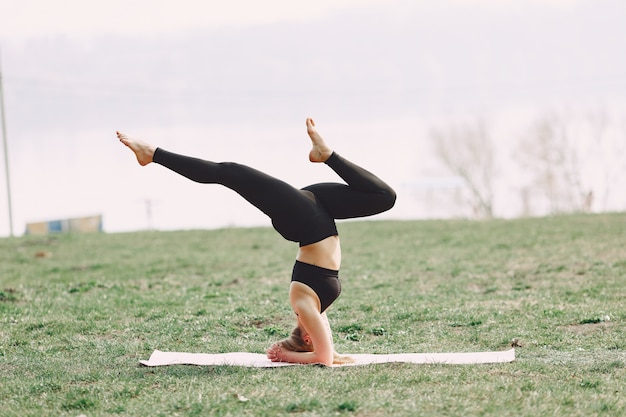 Ragazza sveglia che fa yoga in un parco di estate
