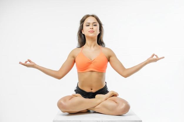 Ragazza sveglia che fa yoga su bianco isolata