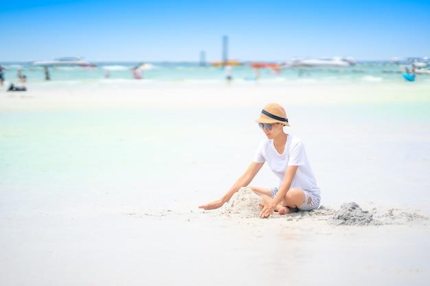 Ragazza sveglia che gioca sabbia sulla spiaggia per tempo di rilassamento in estate su cielo blu