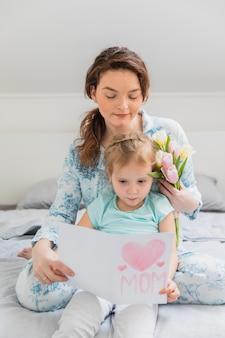 Ragazza sveglia che si siede con sua madre che legge la cartolina d'auguri sul letto