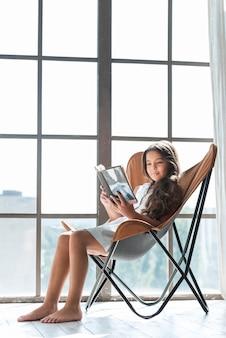 Ragazza sveglia che si siede sul libro di lettura della sedia