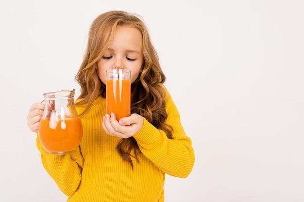 Ragazza sveglia che tiene un vetro e una brocca con il succo di carota su un fondo bianco isolato