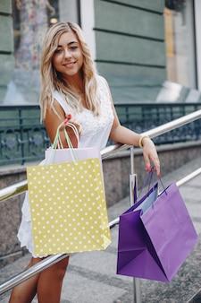 Ragazza sveglia con il sacchetto della spesa in una città