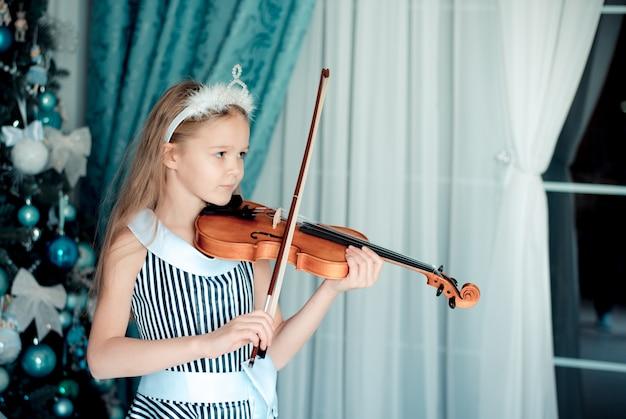 Ragazza sveglia con il violino nella stanza della decorazione di natale.