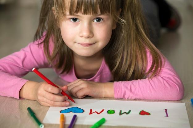 Ragazza sveglia del bambino che disegna con i pastelli variopinti amo la mamma su libro bianco. educazione artistica, concetto di creatività.