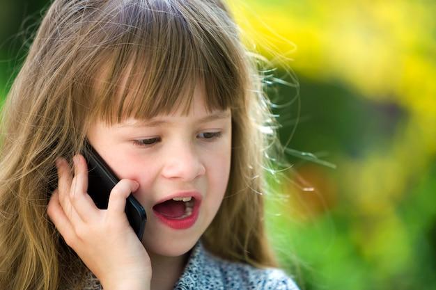 Ragazza sveglia del bambino che parla sul cellulare all'aperto. bambini e tecnologia moderna, comunicazione.