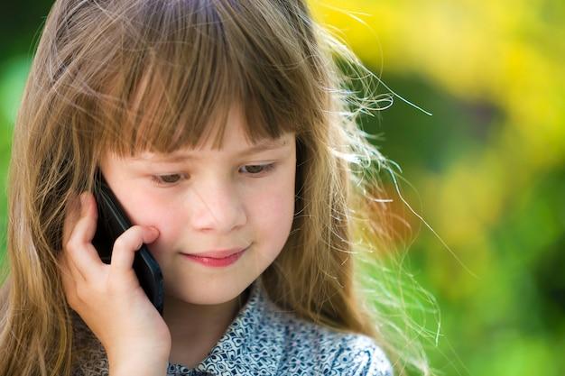 Ragazza sveglia del bambino che parla sul cellulare all'aperto.