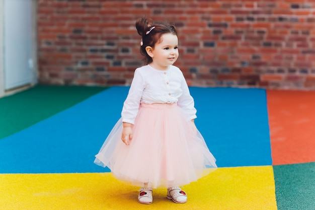Ragazza sveglia del bambino in costume della ballerina al bello giardino di estate.