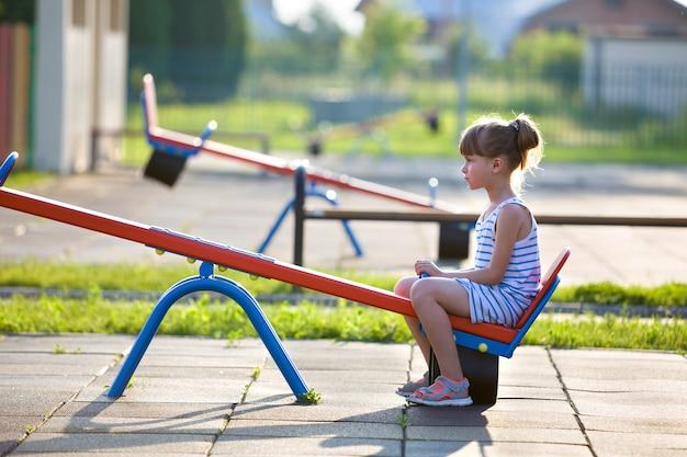 Ragazza sveglia del bambino piccolo all'aperto sull'oscillazione della sega il giorno di estate soleggiato.