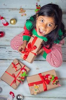 Ragazza sveglia del brunette con i suoi regali il giorno di natale