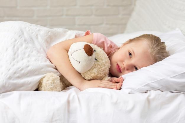 Ragazza sveglia del piccolo bambino che dorme con l'orsacchiotto
