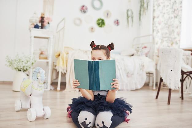 Ragazza sveglia del piccolo bambino che legge un libro nella camera da letto. scherzi con la corona che si siede sul letto vicino alla finestra