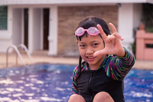 Ragazza sveglia del piccolo bambino con gli occhiali di protezione nella piscina