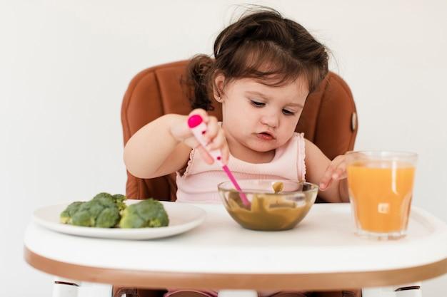 Ragazza sveglia del primo piano che prova a mangiare