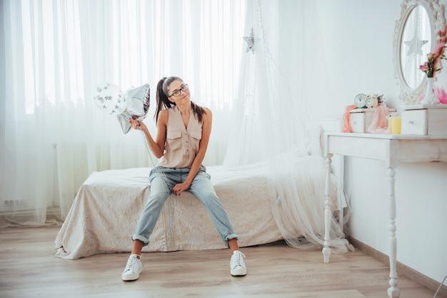 Ragazza sveglia del primo piano del brunette nel, che sorride ampiamente e che gioca con gli aerostati trasparenti e d'argento. indossa occhiali e capelli attorcigliati.