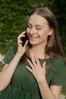Ragazza sveglia dell'adolescente che parla e che sorride sul telefono cellulare all'aperto