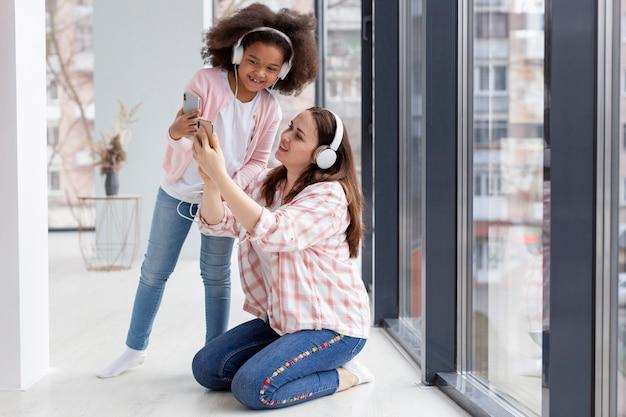 Ragazza sveglia e madre che ascoltano la musica a casa