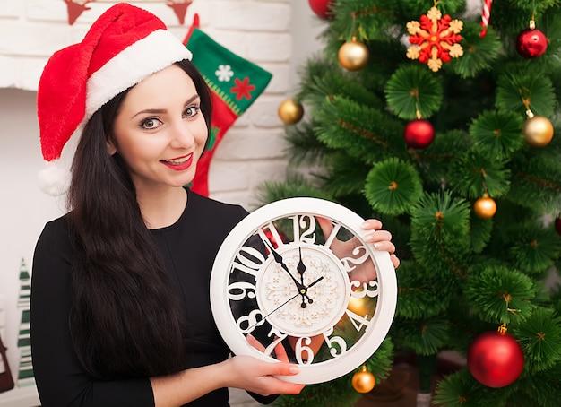 Ragazza sveglia in cappello di santa con l'albero di natale decorato e il vecchio orologio