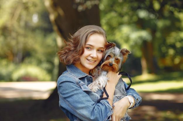 Ragazza sveglia in giacca blu che gioca con il piccolo cane