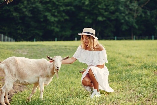 Ragazza sveglia in un campo con capre