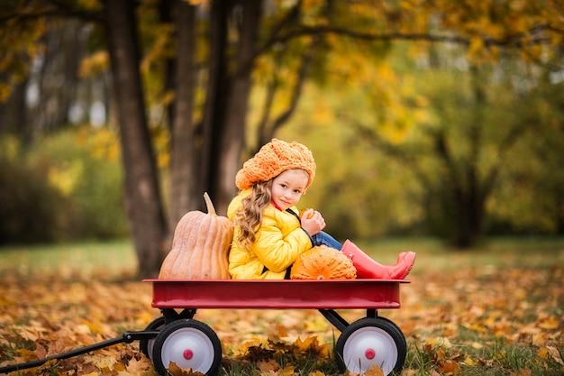 Ragazza sveglia in un impermeabile giallo, stivali di gomma rossi nel parco di autunno