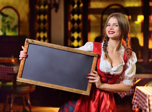 Ragazza sveglia in vestiti bavaresi a oktoberfest con una lavagna