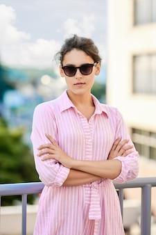 Ragazza sveglia in vestito a strisce rosso ed occhiali da sole che stanno sul balcone
