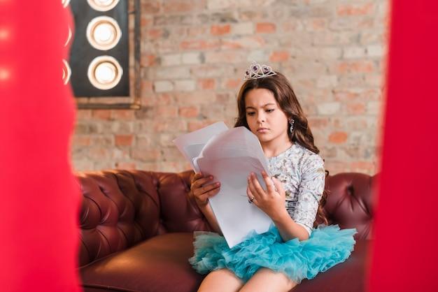 Ragazza sveglia seria che si siede sugli script della lettura del sofà a backstage