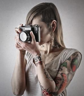 Ragazza tatuata con una macchina fotografica