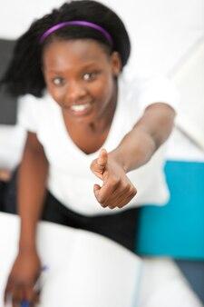 Ragazza teenager allegra con un pollice in su che studia