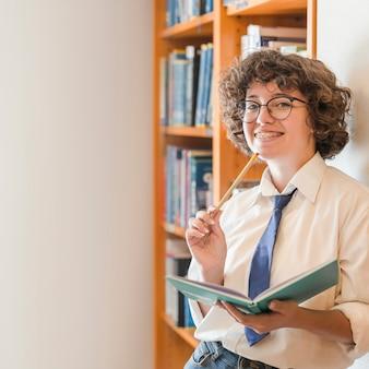 Ragazza teenager allegra in biblioteca
