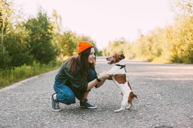 Ragazza teenager attraente che gioca con il suo cane mentre cammina all'aria aperta