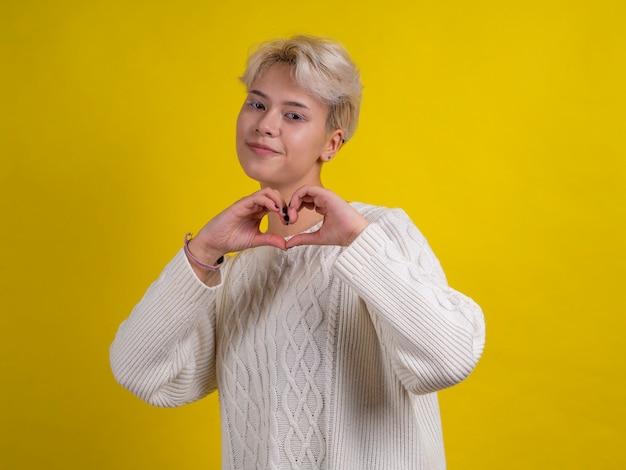 Ragazza teenager bionda sorridente con capelli bianchi in maglione lavorato a maglia bianco che fa gesto del cuore con le mani