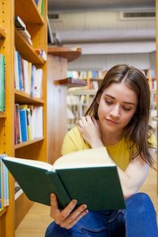 Ragazza teenager che graffia spalla e libro di lettura