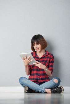 Ragazza teenager che legge libro elettronico interessante che si siede nella posa del loto sul pavimento della sua stanza della città universitaria