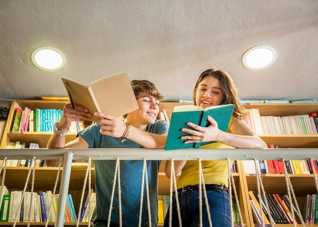 Ragazza teenager che mostra libro al ragazzo