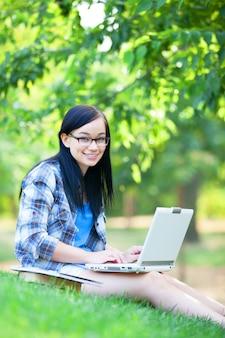 Ragazza teenager con il computer portatile nel parco.
